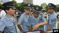 Китайские полицейские изучают афишу концерта Live Earth (Шанхай, 2007 год)