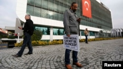 """Стамбул. Сотрудник газеты """"Заман"""" держит плакат против попрания свободы СМИ в Турции"""