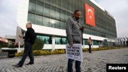 Zaman-ի լրագրողը «Ազատ մամուլը չի կարող լռեցվել» պաստառով կանգնած է թերթի խմբագրության առջև, Ստամբուլ, 14-ը դեկտեմբերի, 2014թ.