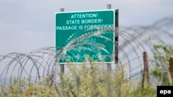 Georgia -- A warning sign is pictured behind a wire barricade erected by Russian and South Ossetian troops along Georgia's de-facto border with its breakaway region of South Ossetia in the village of Khurvaleti, July 14, 2015