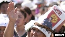 Ош мэринин сүрөтү бар баракчаны башына байлаган аял, 2010-жылдын, 20-августу, Оштогу митингден көрүнүш.
