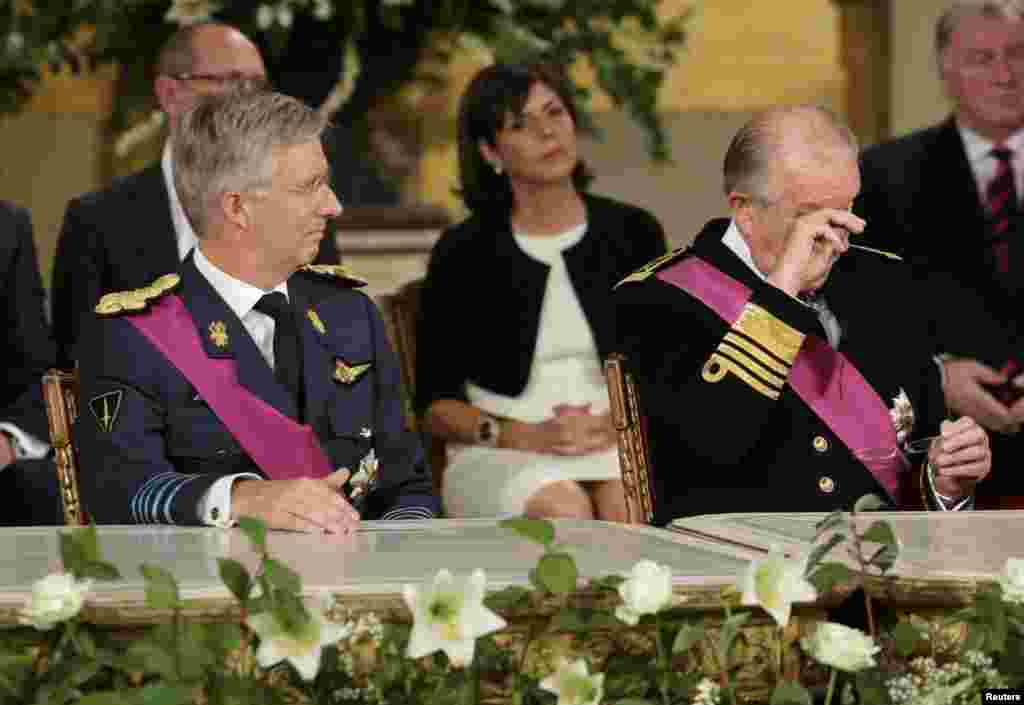 King Albert II (right) of Belgium, watched by son Crown Prince Philippe, wipes his eyes after signing an act of abdication to hand Philippe the throne during a ceremony at the Royal Palace on Belgian National Day in Brussels. (Reuters/Philippe Wojazer)