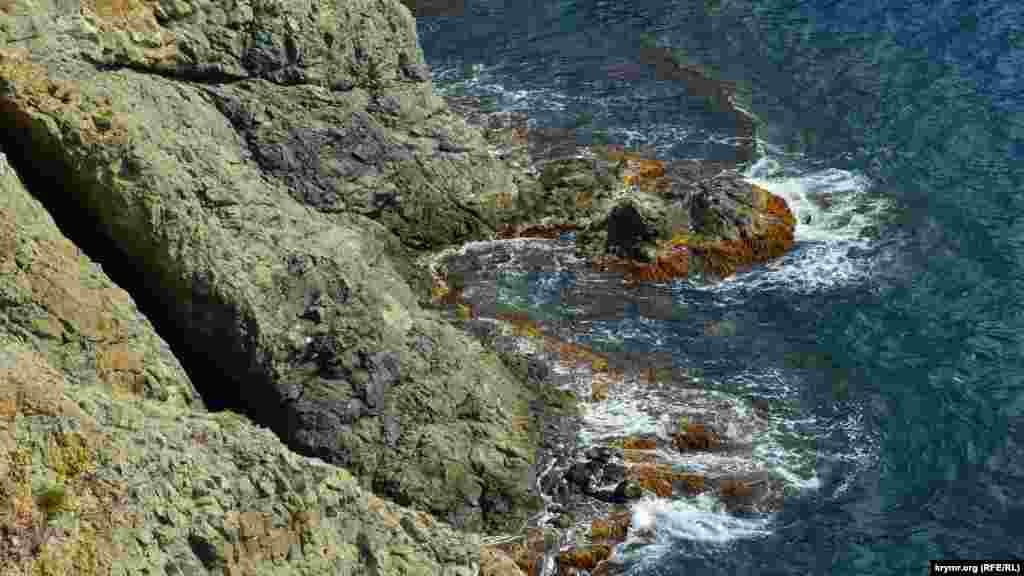 На море легкое волнение и волны бьются о скалы мыса