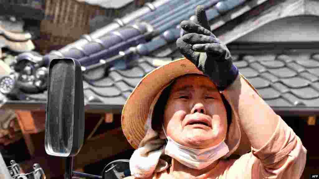 Мощное землетрясение произошло вечером в четверг На фото – женщина плачет, рассказывая о своем разрушенном доме в городе Машики, префектура Кумамото