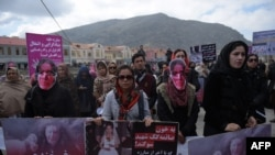 Afghan activists march before artists performed a play depicting the 2015 lynching of Afghan woman Farkhunda Malikzada in Kabul on March 17, 2016.