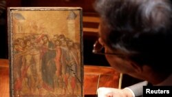 Un expert în arte inspectează o lucrare din secolul XIII