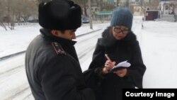 Репортеру Азаттыка Сание Тойкен полицейский вручает повестку на допрос в качестве свидетеля в ДВД Мангистауской области. Актау, 17 февраля 2017 года.