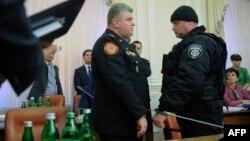 Полицейский надевает наручники на главу службы по чрезвычайным ситуациям