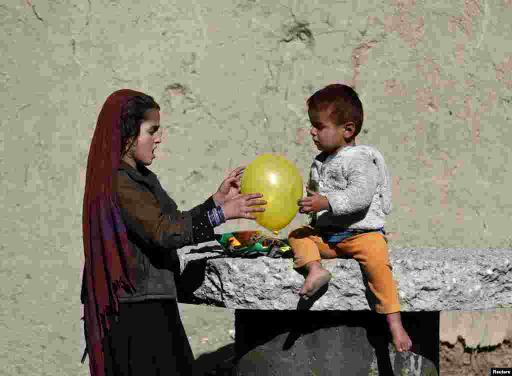 Afghan children play with a balloon outside their house in Kabul. (Reuters/​Omar Sobhani)