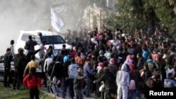 Хомс қаласының эвакуацияны күтіп жүрген тұрғындары БҰҰ көлігінің маңында тұр. Сирия, 10 ақпан 2014 жыл. (Көрнекі сурет)