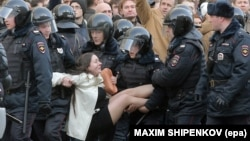 Russian riot police detain a demonstrator during an opposition rally in central Moscow on March 26, 2017.