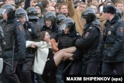 Russian riot policemen detain a demonstrator during an opposition rally in central Moscow in March.