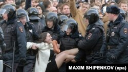 Russian riot policemen detain a demonstrator during the opposition rally in central Moscow on March 26.