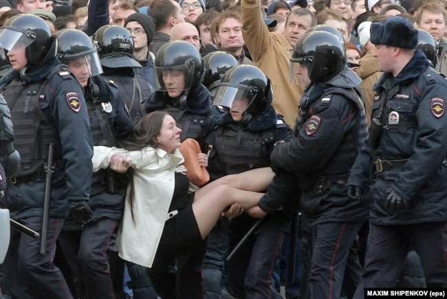Russian riot police detain a young female demonstrator during an opposition rally in central Moscow on March 26