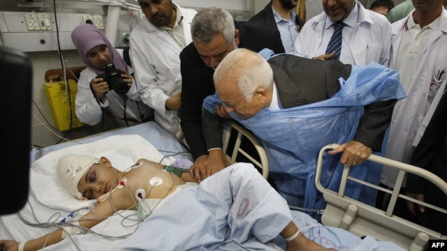 Arab League Secretary-General Nabil Elaraby (center right) and senior Hamas leader Ismail Haniyah (third from left) visit a boy who Palestinian medics say was wounded in an Israeli air strike at a hospital in Gaza City.