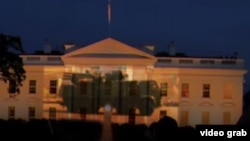 A screen grab from a video posted on YouTube that seemingly shows images of Russian military vehicles projected onto the facade of the White House.