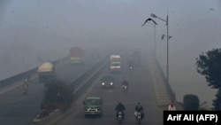 Commuters drive in heavy smog conditions in Lahore on November 21.