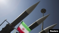 Иран-ирак соғысын (1980-88) еске алу көрмесі кезінде зенит-зымыран кешені жанында ілулі тұрған Иран туы. Тегеран, 28 қыркүйек 2010 жыл.