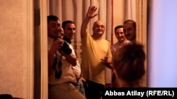 Azerbaijani journalist Eynulla Fatullayev waves to onlookers from his home in Baku after his release from prison in May 2011.