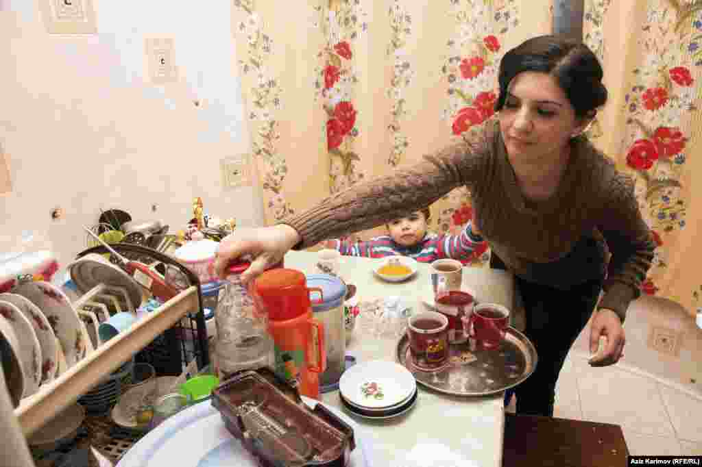 Rafiyeva in the kitchen pouring refreshments