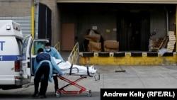 Медицинские работники закатывают носилки с пациентом в машину скорой помощи рядом с одной из больниц Нью-Йорка. 4 апреля 2020 года.
