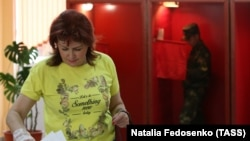 A woman casts her ballot at a polling station during early voting in the presidential election in Minsk on August 4.