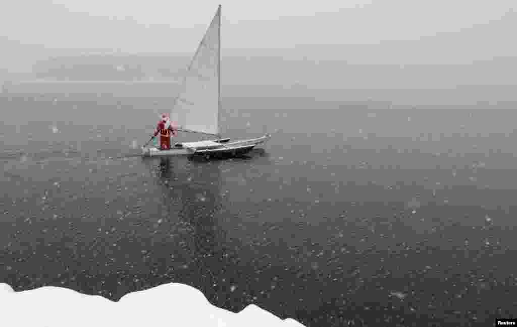 A sailing enthusiast dressed as Santa Claus sails his trimaran to mark the ending of the sailboat season during heavy snowfall on the Yenisei River outside Krasnoyarsk, Russia. (Reuters/Ilya Naymushin)