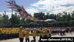 Школьники с символом государственной программы «Рухани жангыру». Алматы, 1 мая 2018 года.
