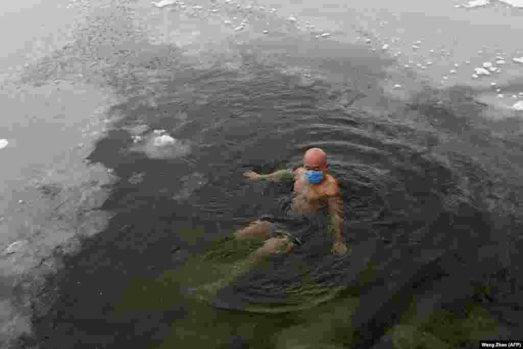 A man wearing a protective face mask swims in a partly frozen lake as snow falls in Beijing, China. (AFP/Wang Zhao)