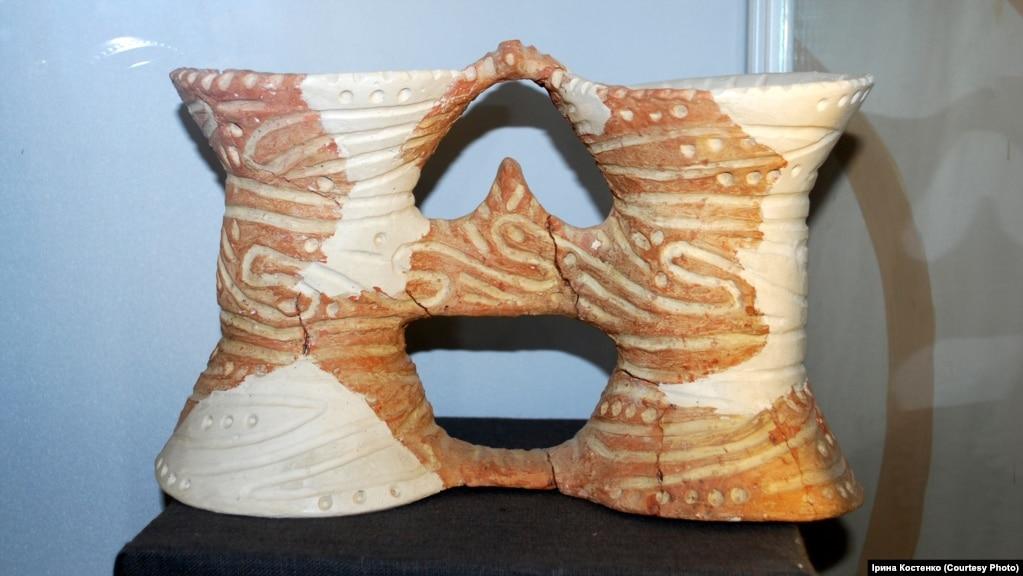 Біноклевидна керамічна посудина, яка дуже подібна до українських подвійних глечиків. У яких ще сто років тому українські селяни носили на поле обід