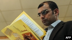 Pakistani investigative journalist Umar Cheema glances at his report prior to addressing a news conference in Islamabad on December 12.