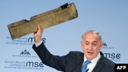 Israeli Prime Minister Benjamin Netanyahu holds up what he claimed was a piece of an Iranian drone shot down in Israeli airspace in February.