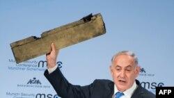 Premierul Benjamin Netanyahu ține un obiect despre care spune că e o piesă din drona iraniană doborît în spațiul aerian în timp ce vorbește la Conferința internațională de securitate de la Muenchen, 18 februarie 2018.