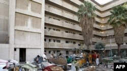 Iraqis salvage items from a building that was hit in a twin truck bombing near the Foreign Ministry in Baghdad.