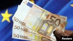 Евро на фоне флага Евросоюза. Иллюстративное фото.