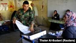 An Iraqi security member casts his vote at a polling station two days before polls open to the public in parliamentary elections in Baghdad on May 10.