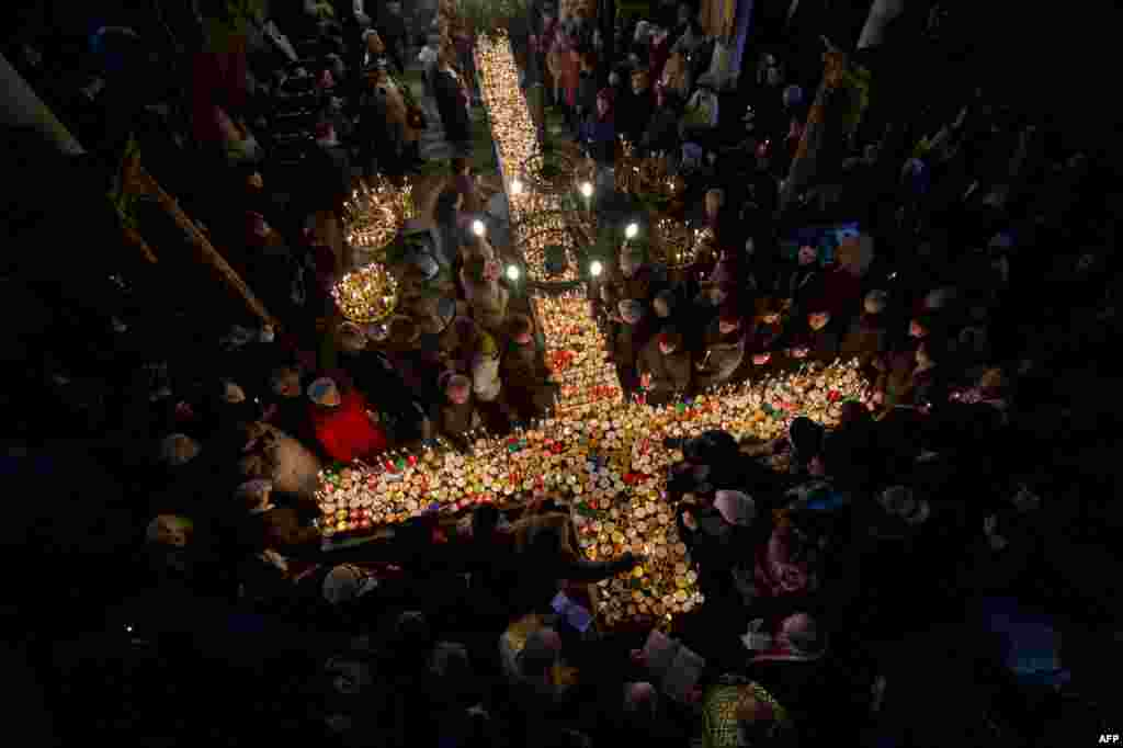 Orthodox Christians pray around a cross-shaped platform covered with candles placed in jars of honey during a ceremony marking the feast day of Saint Haralampi, the Orthodox patron saint of beekeepers, at a church in eastern Bulgaria on February 10. (AFP/Nikolay Doychinov)