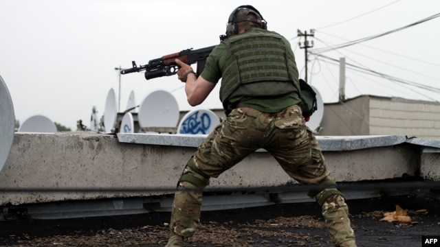 A pro-Russia militant shoots from a roof of a residential building at border guards defending the Federal Border Headquarters building in Luhansk on June 2.