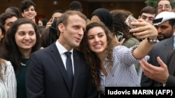 French President Emmanuel Macron poses for selfies with students at Paris-Sorbonne University Abu Dhabi on November 9.
