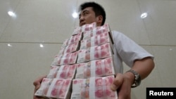 Ақша көтеріп келе жатқан қытай банкінің қызметкері. (Көрнекі сурет)