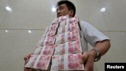 Қытайлық фимра қызметкері 100 юаньдық банкноттарды әкеле жатыр. Тайюань, 4 шілде 2013 жыл. (Көрнекі сурет)