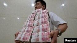 Сотрудник китайского банка несет банкноты юани. Иллюстративное фото.