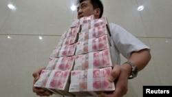 Сотрудник китайской фирмы несет пачки банкнот достоинством в 100 юаней. Тайюань, 4 июля 2013 года.