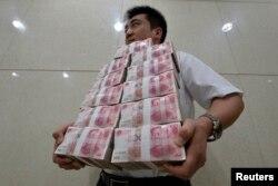 Қытай юанін көтеріп келе жатқан банк қызметкері. Қытай, 4 шілде 2013 жыл. (Көрнекі сурет)