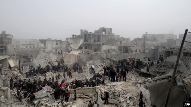 People inspect the destruction following an apparent surface-to-surface missile strike on the northern city of Aleppo on February 19.