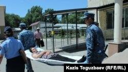 Транспортировка конвойными заключенной Гаухар Худабаевой по территории районной больницы. Поселок Отеген-батыра Алматинской области, 20 июня 2019 года.