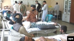 Afghan civilians injured in a coalition air strike receive treatment in Kandahar