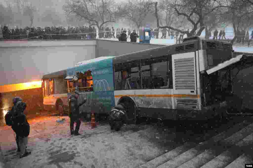 Emergency workers attend the scene of a deadly bus crash that occurred on December 25 after the vehicle careered off a road and onto steps leading into an underground passageway in the Russian capital, Moscow. (TASS/Mikhail Pochuyev)