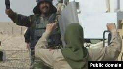 """Иранка, состоящая в движении """"Национальная армия освобождения Ирана"""", и иракский военнослужащий в лагере Ашраф в Ираке."""
