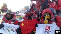 صعودکنندگان قرمز پوش پس از رسيدن به قله برفپوش اورست پرچم های چين و المپيک را گشودند و رو به دوربين ها فرياد کشيدند: زنده باد چين، زنده باد تبت. (عکس از AFP)